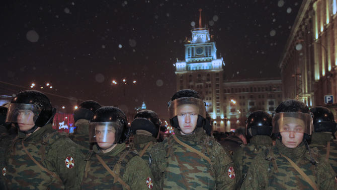 Russian police  block the way during an unsanctioned rally in downtown  Moscow,  Russia, Monday, Dec. 31, 2012, with the Stalin's architecture hotel in the background. The Russian opposition protests on the 31st of each month are a nod to the 31st article of the Russian constitution, which guarantees the right of assembly. (AP Photo/Alexander Zemlianichenko)
