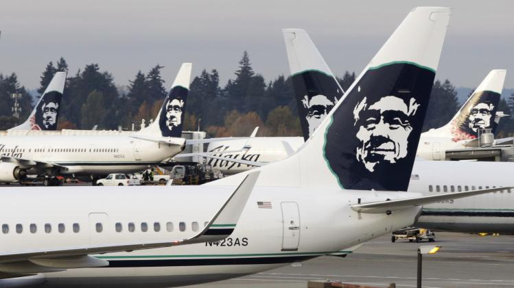 A ground crew member walks near Alaska Airlines planes parked at Seattle-Tacoma International Airport