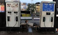 An Indian employee sleeps at a closed fuel station during a nationwide strike against petrol prices. State-run Indian refiners have partially rolled back a huge hike in petrol prices following widespread public protests and anger among the national government's coalition members
