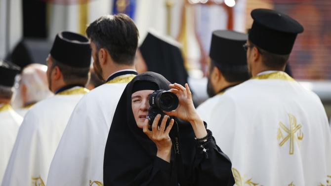 A nun takes pictures as believers mark 1,700 years since the Edict of Milan in Nis