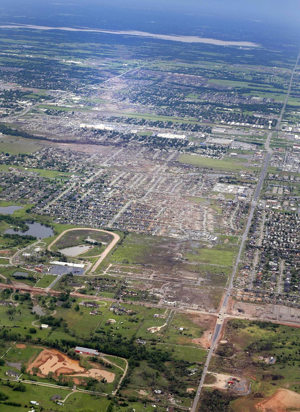 This Tuesday, May 21, 2013 aerial photo shows, from bottom to top, the path Monday's tornado took through Moore, Okla. The huge tornado roared through the Oklahoma City suburb Monday, flattening entire neighborhoods and destroying an elementary school with a direct blow as children and teachers huddled against winds. (AP Photo/Kim Johnson Flodin)