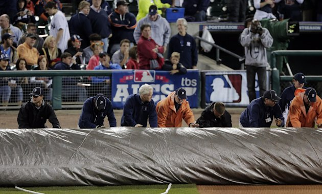 Grounds crew roll out a tarp after Game 4 of the American League championship series between the Detroit Tigers and the New York Yankees was postponed due to rain Wednesday, Oct. 17, 2012, in Detroit. (AP Photo/Charlie Riedel)