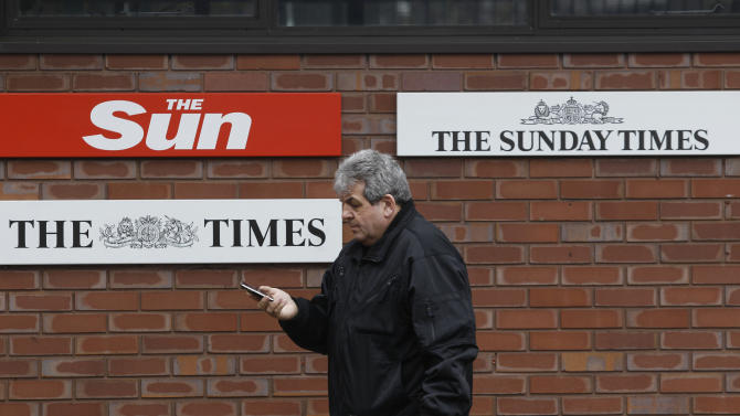 FILE - In this Friday, Feb. 17, 2012 file photo, a man walks past signs of Rupert Murdoch's News International's titles, outside their headquarters in London. News Corp. is reporting their fourth quarter 2012 earnings on Wednesday, Feb. 6, 2013. (AP Photo/Lefteris Pitarakis, File)