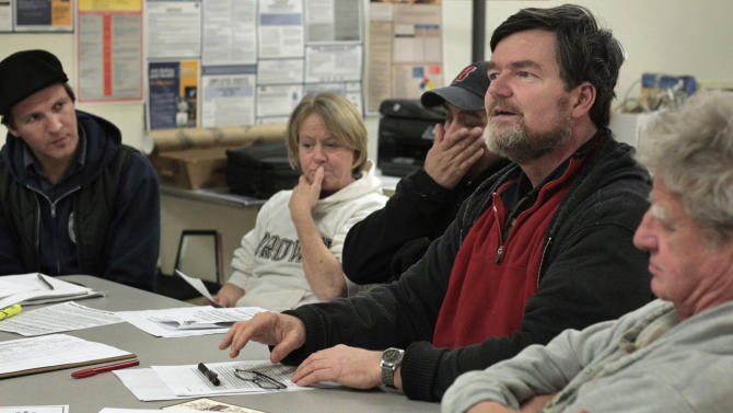 In this Feb. 5, 2013 photo, John Gallagher, second from right, an unemployed part-time student from Providence, R.I., addresses a group on the difficulties of accessing unemployment benefits in Rhode Island during a meeting at the George Wiley Center in Pawtucket, R.I.  A month after losing his job as a bus driver, Gallagher has not been able to reach anyone at the state's unemployment call center. Also attending the meeting are, from left, Camilo Viveiros of Somerset, Mass., head organizer at the center; Maggi Rogers of Pawtucket, also an organizer; unemployed construction worker Ledimo Hernandez of Cranston, R.I.; and retiree Charles Casey of Providence. (AP Photo/Steven Senne)
