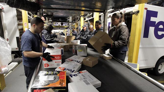FILE - In this Dec. 13, 2011 file photo, FedEx employees sort packages at the FedEx hub at Los Angeles International Airport in Los Angeles. FedEx Corp., said Monday, Aug. 13, 2012, they will soon begin offering buyouts to U.S. employees in an effort to cut costs. (AP Photo/Jae C. Hong, File)