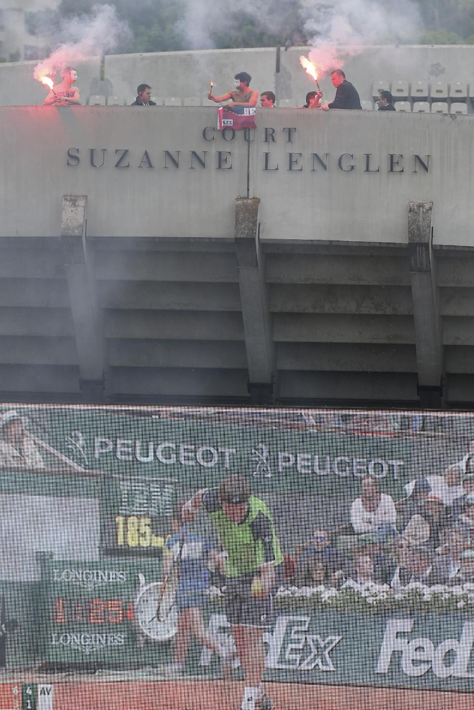 Security officiers remove demonstrators display a banner demanding the resignation of French President  Francois Hollande, atop Suzanne Lenglen court, as Spain's Rafael Nadal plays compatriot David Ferrer on center court during the men's final match of the French Open tennis tournament at the Roland Garros stadium Sunday, June 9, 2013 in Paris. (AP Photo/David Vincent)