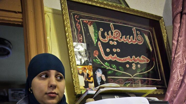 Janna Hakim, 18, shows a poster featuring a picture of her mother Faten on Thursday, Aug. 16, 2012 in New York.  On Aug. 13, 2010, Faten was taken away from home by ICE officials and deported to Ramallah, Palestine.  Janna has since engaged in public efforts to reunite the family. (AP Photo/Bebeto Matthews)