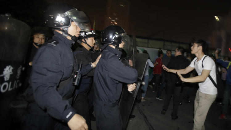 Chinese anti-riot police men force protesters to leave the area outside the city government office in Zhejiang province's Ningbo city,  Sunday, Oct. 28, 2012, where residents had gathered to protest the proposed expansion of a petrochemical factor. Thousands of protesters marched through an eastern Chinese city on Sunday, shouting for fellow citizens to join them in demanding that the government halt the expansion of a petrochemical factory because of pollution fears. (AP Photo/Ng Han Guan)