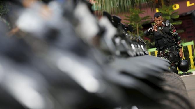 Indonesian soldier helps to line up his unit's motorcycles at the venue for the Asian-African conference in Jakarta