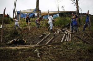 """A family of MTST work on a newly built shack at the """"People's World Cup"""" camp in Sao Paulo"""