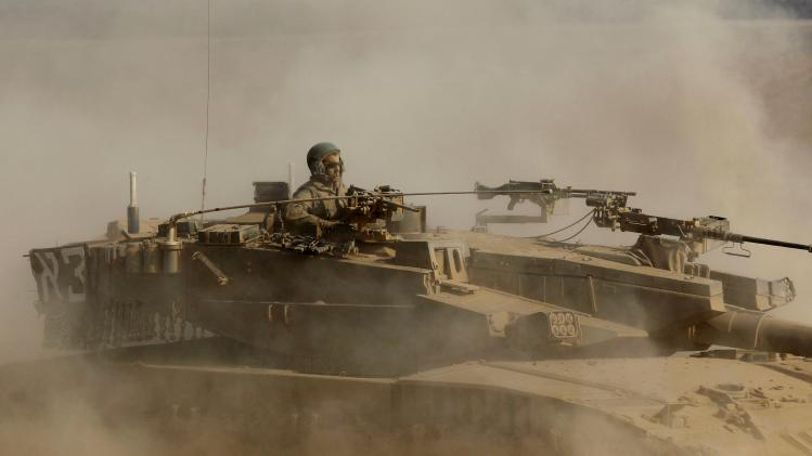 An Israeli soldier rides atop a moving tank near the border with Gaza