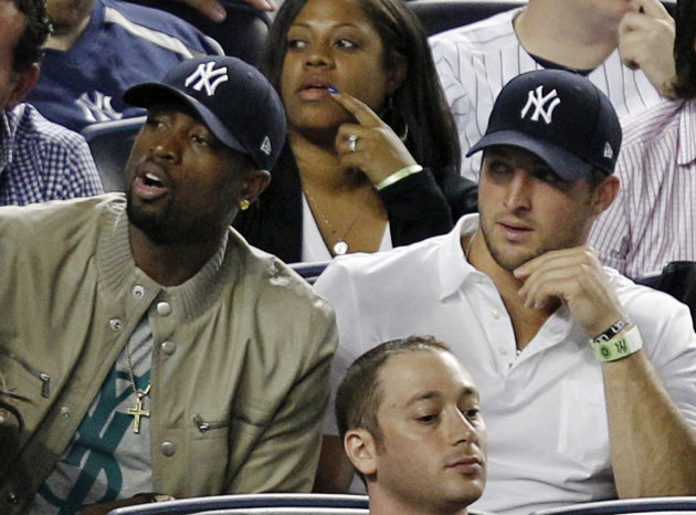 Miami Heat's Dwayne Wade, left, sits beside New York Jets quarterback Tim Tebow during the New York Yankees baseball game against the Los Angeles Angels at Yankee Stadium in New York, Sunday, April 15