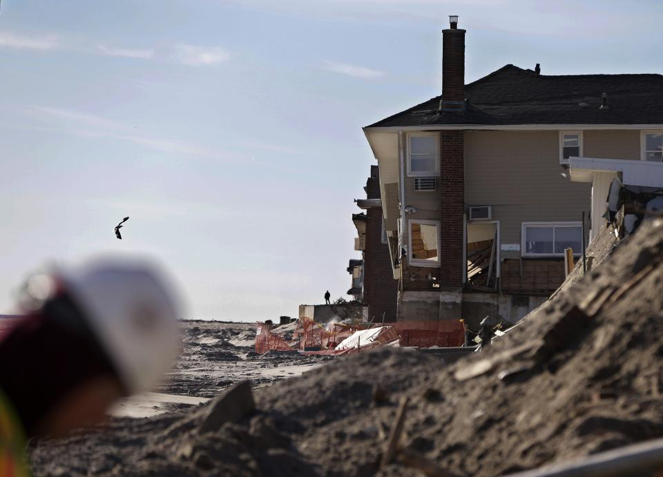 A construction worker walks on the beach as work continues in the Rockaways cleaning up debris from destroyed homes in the wake of Superstorm Sandy, Thursday, Jan. 10, 2013, in New York.  The November storm damaged or destroyed 305,000 housing units in New York.  (AP Photo/Kathy Willens)