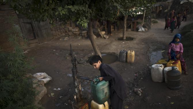 In this Saturday, Aug. 23, 2014 photo, a boy gets water from a hand pump near Islamabad, Pakistan. On the outskirts of the slums of Pakistan's biggest city, protesters burning tires and throwing stones have what sounds like a simple demand: They want water at least once a week. In Karachi people go days without getting water from city trucks, sometimes forcing them to use groundwater contaminated with salt. (AP Photo/Muhammed Muheisen)
