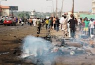 Residents look on at the scene of the explosion on Junction Road in northern Nigerian city of Kaduna. A car bombing near a church in northern Nigeria as services were being held on Easter Sunday killed at least 20 people, wounded 30 others and put the country on alert over fears of further attacks