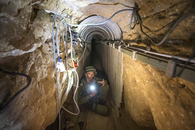 An Israeli army officer gives journalists a tour of a tunnel allegedly used by Palestinian militants for cross-border attacks, July 25, 2014. (AP/Jack...