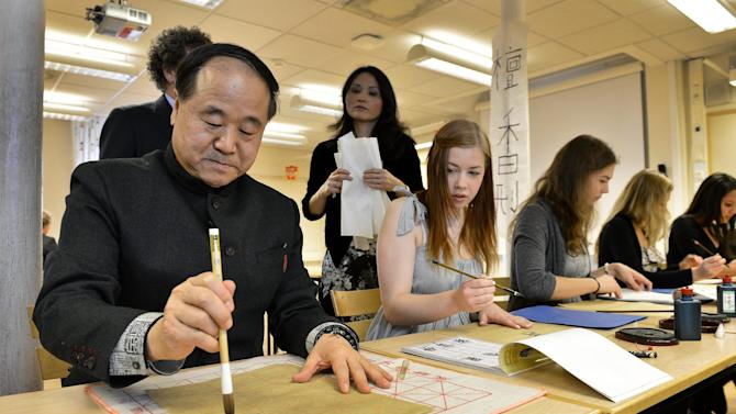Winner of the Nobel Prize 2012 for literature, Mo Yan demonstrates Chinese calligraphy for students during a visit to Hersby Gymnasium high school in Lidingo, outside Stockholm, Sweden , Friday, Dec. 7, 2012. In the background is Rona Shan Long Shi, teacher in mandarin language. (AP Photo/Anders Wiklund) SWEDEN OUT