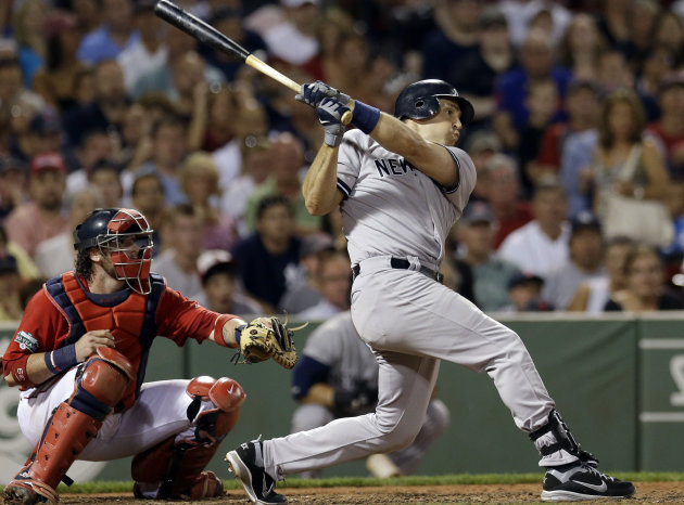 New York Yankees' Mark Teixeira follows through on a two-run triple as Boston Red Sox catcher Jarrod Saltalamacchia watches in the seventh inning of a baseball game at Fenway Park in Boston Friday, July 6, 2012. (AP Photo/Elise Amendola)