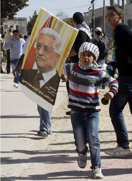 A Palestinian girl holds a placard depicting Palestinian President Abbas during a demonstration marking the anniversary of late Palestinian leader Arafat's death, near Nablus