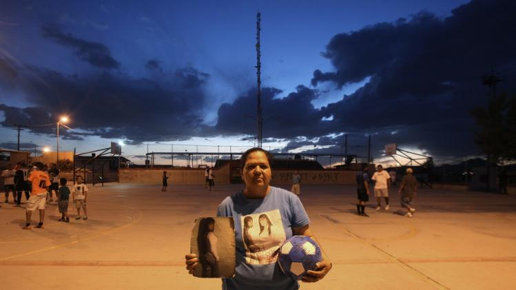 Norma Laguna holds a photograph of her daughter Idaly while posing for a photograph at a field where Idaly used to play soccer, in Ciudad Juarez