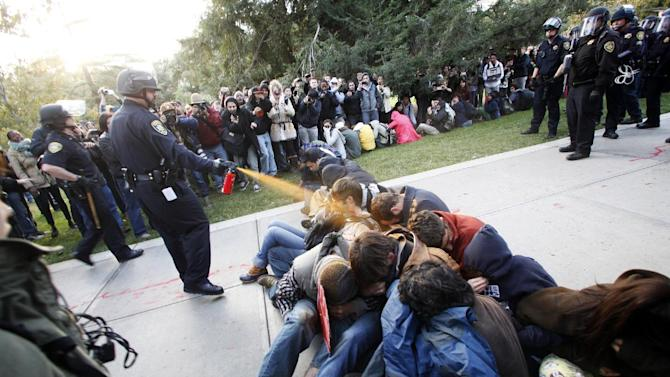 FILE - In this Nov. 18, 2011 file photo, University of California, Davis Police Lt. John Pike uses pepper spray to move Occupy UC Davis protesters while blocking their exit from the school's quad in Davis, Calif. The University of California plans to publish a long-awaited report on the pepper-spraying of student demonstrators by UC Davis police last fall  online at noon Wednesday, April 11, 2012 a day after an Alameda County judge approved its publication without the names of most officers involved in the Nov. 18 clash. (AP Photo/The Enterprise, Wayne Tilcock, File)
