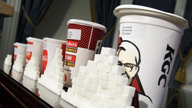 FILE - This photo from  Thursday, May 31, 2012, shows a display of various size cups and sugar cubes at a news conference at New York's City Hall. The city Board of Health is scheduled to hold a hearing Tuesday, July 24, 2012 on the proposal to ban the sale of sugary drinks larger than 16 ounces at city restaurants, movie theaters and other eateries. (AP Photo/Richard Drew, File)