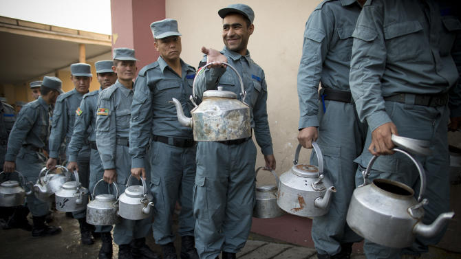 Afghan National Police officers line up with tee pots to get their breakfast at the Police Academy in Kabul, Afghanistan, Tuesday, Oct. 9, 2012. NATO defense leaders gathering in Brussels Tuesday are committed to the war in Afghanistan, according to U.S. and alliance officials, but there are growing signs that the Afghan political and military hostilities against the coalition are starting to wear on the coalition. (AP Photo/Anja Niedringhaus)
