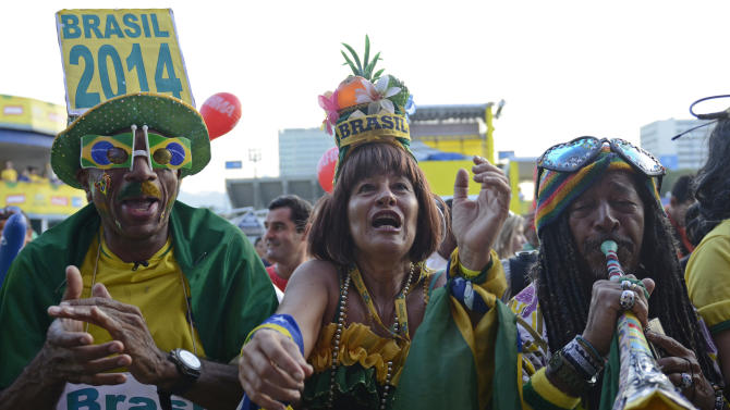 Brazilian fans cheer as they watch the Confederations Cup semifinal match between Brazil and Uruguay on a giant screen celebrate a goal by the Brazilian team in Rio de Janeiro, Brazil, June 26, 2013. (AP Photo/Nicolas Tanner)