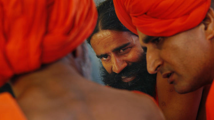 Indian spiritual guru Baba Ramdev, center, talks to his associates during a public session at his ashram in Haridwar, India, Thursday, June 9, 2011. Ramdev, who began a hunger strike against corruption Saturday, and thousands of his followers were forced from a New Delhi park in a Sunday raid that injured dozens and sparked even more public outrage. He resumed his protest Monday from his ashram and said he was arming thousands of supporters to block any police action to disrupt the fast. (AP Photo/Gurinder Osan)