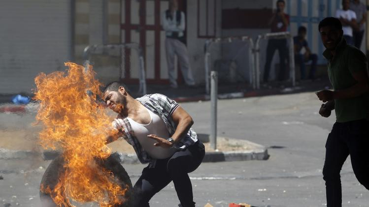 Man pushes a burning tyre during a protest against the Israeli offensive in Gaza, in the West Bank City of Hebron