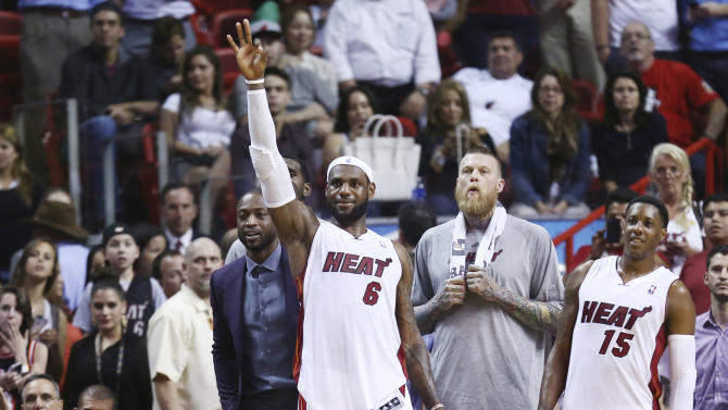 Miami Heat players Dwyane Wade, left, LeBron James (6), Chris Andersen and Mario Chalmers (15) watch the end of an NBA basketball game in Miami, Monday, March 3, 2014 against the Charlotte Bobcats. LeBron James scored a team recond of 61 points. The Heat won 124-107. (AP Photo/J Pat Carter)
