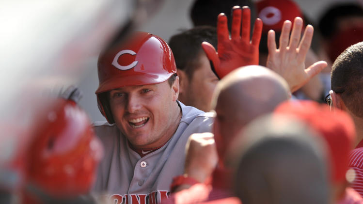 Cincinnati Reds' Jay Bruce celebrates with teammates in the dugout after hitting a solo home run during the seventh inning of a baseball game against the Chicago Cubs in Chicago, Sunday, April 20, 2014. Cincinnati won 8-2. (AP Photo/Paul Beaty)