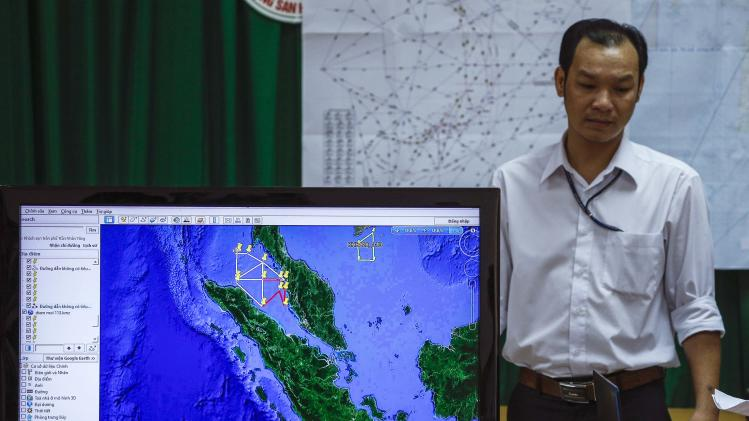 A Vietnamese officer stands next to a TV screen showing a flight route during a news conference about their mission to find missing Malaysia Airlines flight MH370 at Phu Quoc Airport