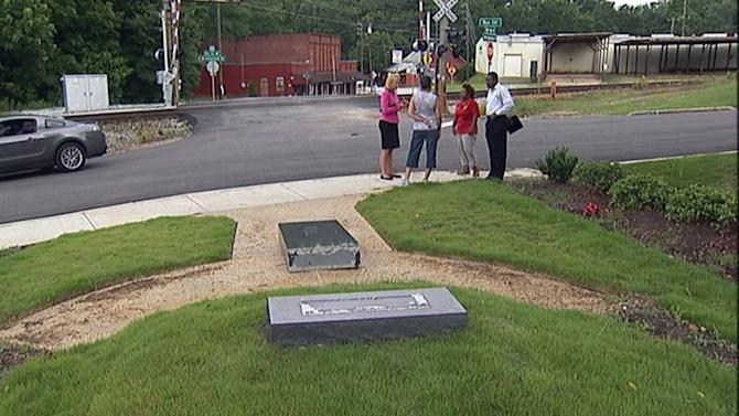 In this image taken from video provided by WSB-TV, people stand near the location of a knocked-over monument dedicated to Melvinia Shields, the great-great-great grandmother of first lady Michelle Obama, Monday June 10, 2013 in Rex, Ga. Police are investigating the incident. (AP Photo/WSB-TV) MANDATORY CREDIT: WSB-TV