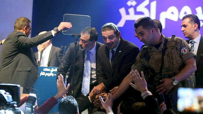 Lebanon's former prime minister Saad al-Hariri, escorted by his bodyguards, greets his supporters during the 11th anniversary of the assassination of his father, Rafik al-Hariri, in Beirut
