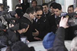Baris Guler, son of Turkey's Interior Minister Muammer Guler, is escorted by plainclothes police officers as he leaves following a medical control in Istanbul