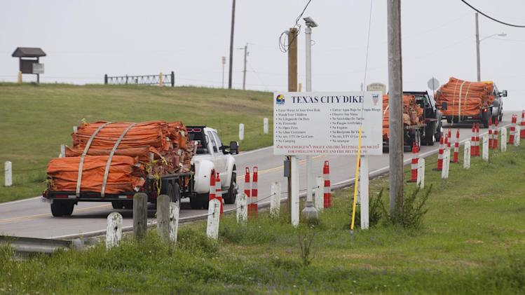 Environmental personnel drive onto the Texas City Dike with oil containment booms for oil remediation following a barge collision in the ship channel, causing an oil spill Saturday, March 22, 2014, in Houston. The barge carried 924,000 gallons of fuel oil. (AP Photo/ Houston Chronicle, Brett Coomer)