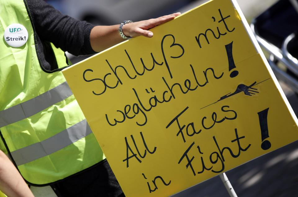 "A Lufthansa cabin crew member holds a poster during a demonstration as flight attendants of German Lufthansa airline went on an 24-hour-strike for higher wages at the airport in Munich, southern Germany, on Friday, Sept. 7, 2012. First sentence on the poster reads ""Finish smiling away"". (AP Photo/Matthias Schrader)"