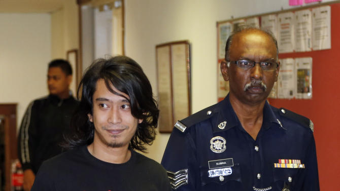 Activist Adam Adli, left, smiles before being released on bail at a court house in Kuala Lumpur, Malaysia,Thursday, May 23, 2013. Prosecutors filed a sedition charge Thursday against a student activist who urged Malaysians to engage in street protests against the government over claims of election fraud. (AP Photo/Vincent Thian)