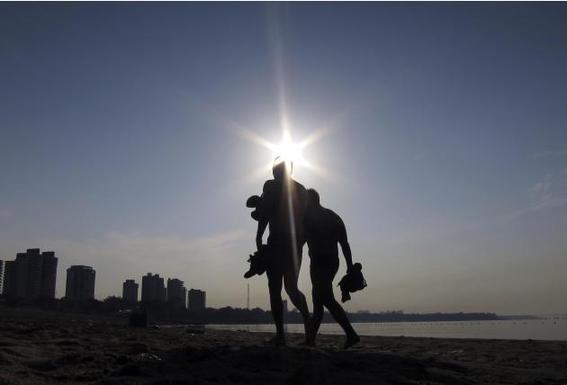 Two swimmers walk along a beach next to the Amazon River at sunrise in Manaus, Brazil