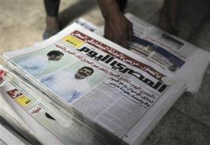 A shopkeeper sells copies of Al-Masry Al-Youm with pictures of ousted President Mursi in white prison uniform, along Mohamed Mahmoud street near Tahrir Square in Cairo