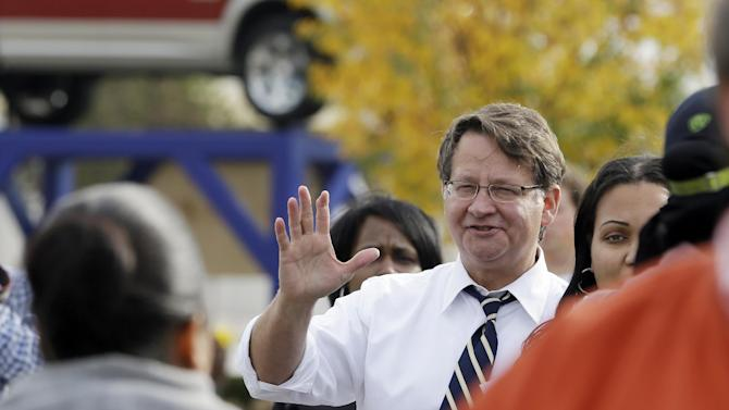 Michigan Democratic Senate candidate Gary Peters greets United Auto Workers after their shift at Chysler Group's Warren Truck Assembly plant in Warren, Mich., Tuesday, Oct. 28, 2014. (AP Photo/Carlos Osorio)