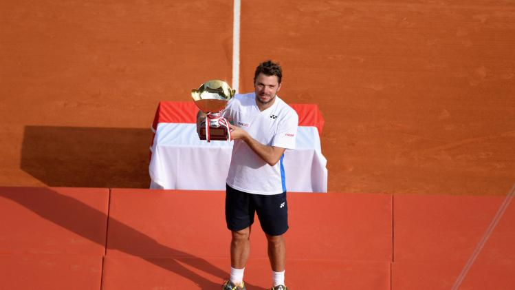 Wawrinka of Switzerland hold up his trophy after winning the final tennis match against compatriot Federer at the Monte Carlo Masters in Monaco