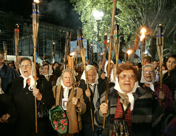 FILE - This a Monday, April 30, 2007 file photo of Argentina&#39;s Mothers of Plaza de Mayo hold torches as they rally with torches to mark the 30th anniversary of their first protest around Buenos Aires Plaza de Mayo to demand the return of their disappeared children on April 30, 1977. Tens of thousands of people throughout the world are listed as missing in armed conflicts and after illegal arrests, detentions, abduction or any other form of deprivation of human rights and liberty. On the International Day of the Disappeared on Thursday Aug.30, 2012 the International Commission on Missing Persons (ICMP) called on all governments to provide answers to families on the fate and whereabouts of the missing persons.(AP Photo/Eduardo Di Baia, File)