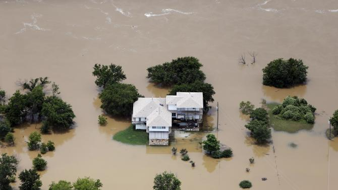 Flood waters from the Brazos River encroach upon a home in the Horseshoe Bend neighborhood, Friday, May 29, 2015, in Weatherford, Texas. Floodwaters submerged Texas highways and threatened more homes Friday after another round of heavy rain added to the damage inflicted by storms. (AP Photo/Brandon Wade)