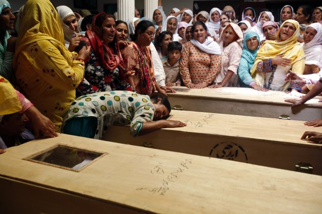 Relative of one of seventeen children who died after a gas cylinder exploded on a school bus, cries over the coffin, on the outskirts of Gujrat