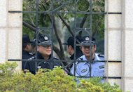Police look out from the city government offices in Ningbo, in eastern China's Zhejiang province on October 29. China's eastern city of Ningbo detained more than 50 people over violent protests last week that successfully blocked a planned chemical plant, state media said Tuesday