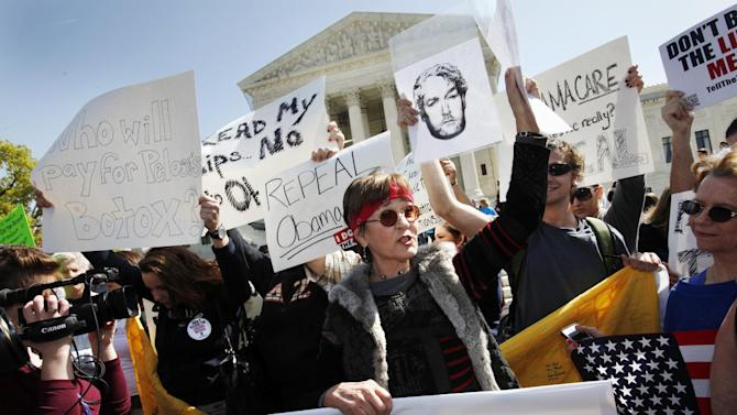 Protesters who identified themselves as being with the Tea Party Patriots, including Linda Dorr, of Laguna Beach, Calif., center, demonstrate against the health care law outside of the Supreme Court in Washington, Monday, March 26, 2012, as the court began hearing arguments on President Obama's health care legislation. (AP Photo/Jacquelyn Martin)