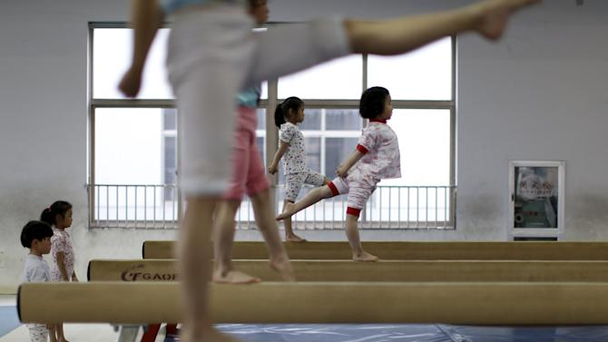 Young gymnasts practice on balance beams at a gymnasium of a sports school in Jiaxing