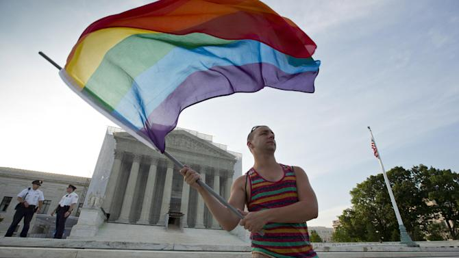 FILE- In this June 26, 2013, file photo, gay rights advocate Vin Testa waves a rainbow flag in front of the Supreme Court in Washington. Thousands of businesses, religious groups, advocacy organizations and politicians who are filing legal briefs at the Supreme Court in support of gay marriage. The cases from Kentucky, Michigan, Ohio and Tennessee will be argued April 28, and a decision is expected by early summer.  (AP Photo/J. Scott Applewhite, File)